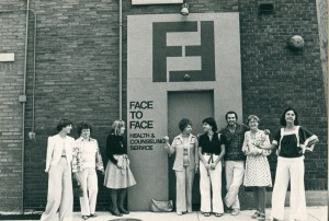 Standing in front of the original location of Face to Face, 8 staff members dressed outrageously 70s clothing pose together for a photo.