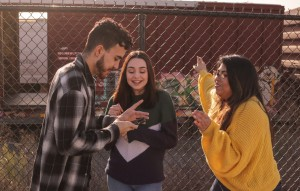A group of three young people talk animatedly together outside in front of fence.